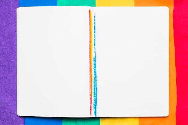 Open voorbeeldenboek met regenboogstrepen Gratis Foto