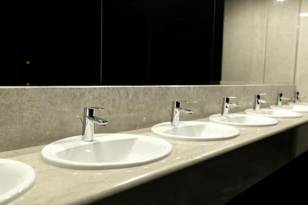 Openbaar toilet en badkamer interieur met wastafel. Premium Foto