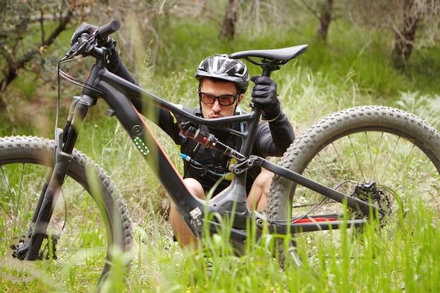 Openhartig openluchtschot van geconcentreerde jonge ruiter in beschermende uitrustingzitting op gras voor zijn gebroken elektrische fiets, proberend om erachter te komen wat het probleem is. mens die e-fiets controleert vóór cycli Gratis Foto