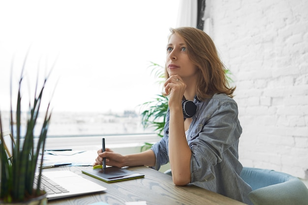 Openhartig schot van aantrekkelijke bekwame jonge vrouwelijke ontwerper zit aan bureau voor opengeklapte laptop, pen vasthouden terwijl puttend uit grafisch tablet, bezig met interieur ontwerpproject thuis kantoor Gratis Foto