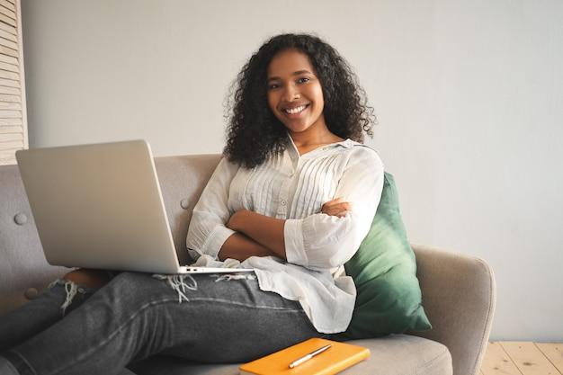 Openhartig schot van gelukkige succesvolle jonge donkere vrouwelijke blogger zittend op de bank met modern elektronisch apparaat op haar schoot, armen gekruist en glimlachend vol vertrouwen, surfen op internet Gratis Foto