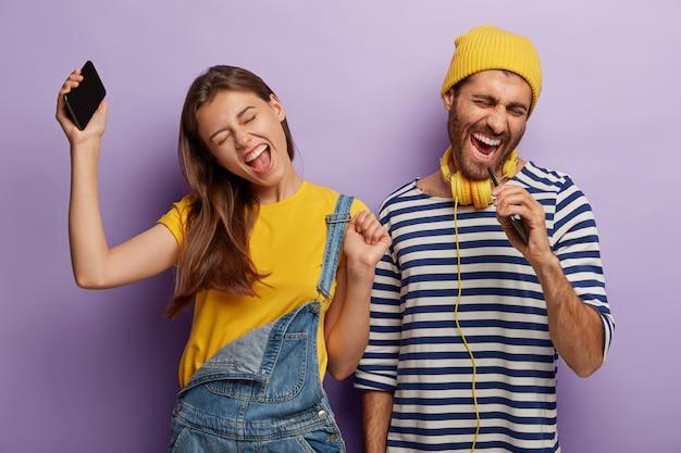 Openhartig shot van dolgelukkig energiek vriendje en vriendin luisteren muziek via mobiele telefoon, dansen en zingen luid, uiten positieve emoties, staan naast elkaar, heffen armen op en bewegen actief Gratis Foto