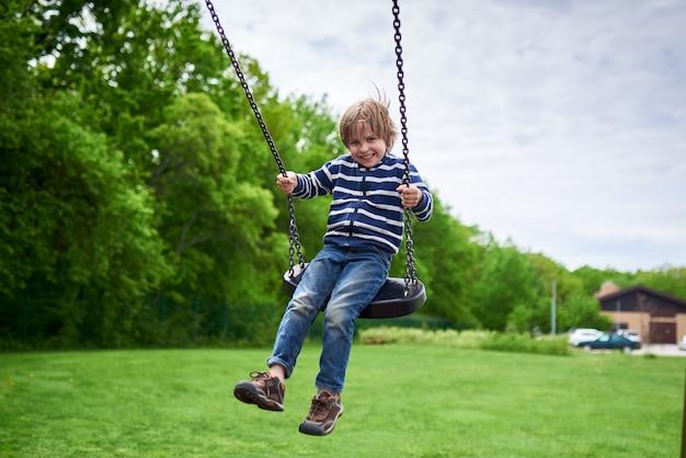 Openlucht portret van schattige peuter lachende jongen swingend op een schommel op de speelplaats Premium Foto