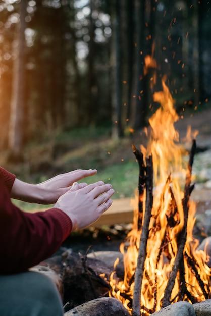 Openlucht verticaal beeld van reiziger die zijn handen verwarmen dichtbij dichtbij kampvuur binnen een bos. Premium Foto
