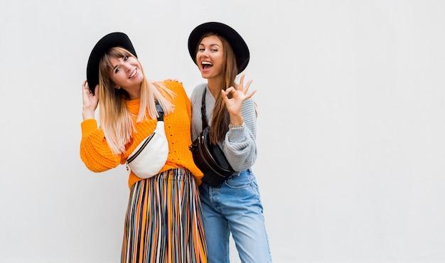 Openluchtfoto van twee vrolijke vrouwelijke vrienden die grote tijd doorbrengen die samen op wit stellen Gratis Foto