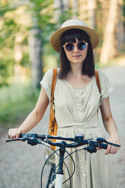 Openluchtportret van aantrekkelijk jong brunette in een hoed op een fiets. Gratis Foto