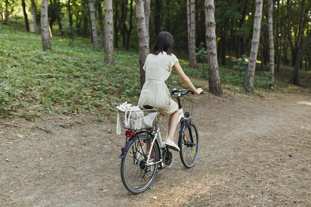Openluchtportret van aantrekkelijk jong brunette op een fiets. Gratis Foto