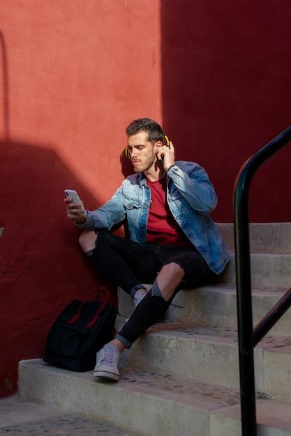 Openluchtportret van de moderne jonge mens met slimme telefoonzitting in de straat. Premium Foto