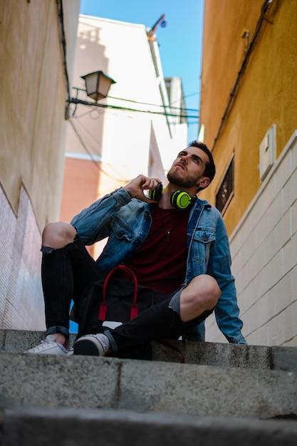 Openluchtportret van de moderne jonge mens met slimme telefoonzitting in de straat Premium Foto