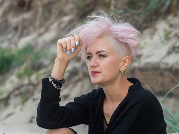Openluchtportret van een mooie sexy jonge vrouw met roze haar en geschoren tempels die hipster meisje roken Premium Foto