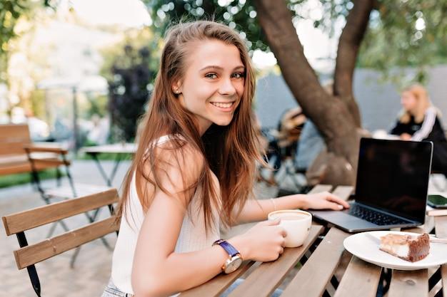 Openluchtportret van gelukkig glimlachend meisje met lang haar en grote ogen die buiten met laptop werken Gratis Foto