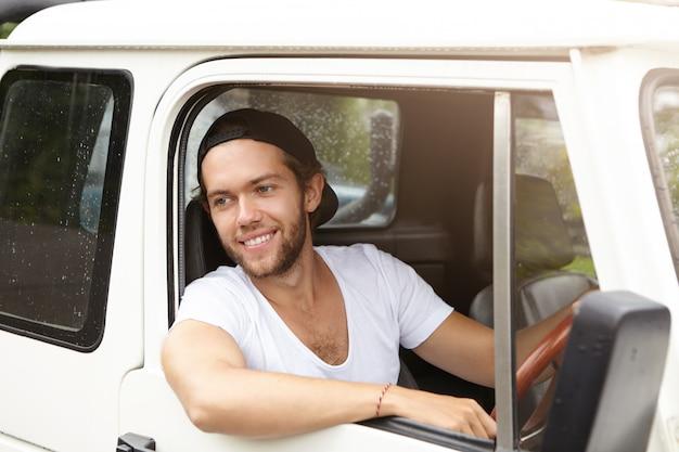 Openluchtportret van knap jong gebaard mannetje in honkbal glb dat uit zijn hoofd uit open venster van zijn het witte auto glimlachen steekt Gratis Foto