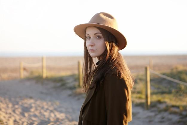 Openluchtportret van modieuze jonge europese vrouw die trendy hoed en zwarte jas dragen die met subtiele glimlach kijken terwijl het hebben van aardige avondwandeling aan zee, dromend en zonsondergang bewonderen Gratis Foto