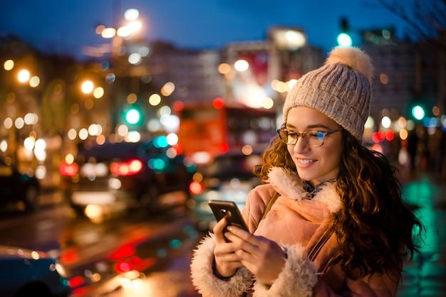 Openluchtportret van mooie jonge vrouw die haar mobiele telefoon met behulp van bij nacht dichtbij stadsweg. Premium Foto