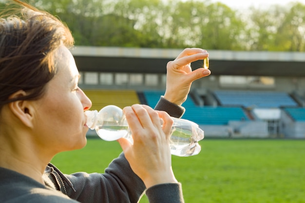 Openluchtportret van rijpe vrouw die vitamine e nemen Premium Foto