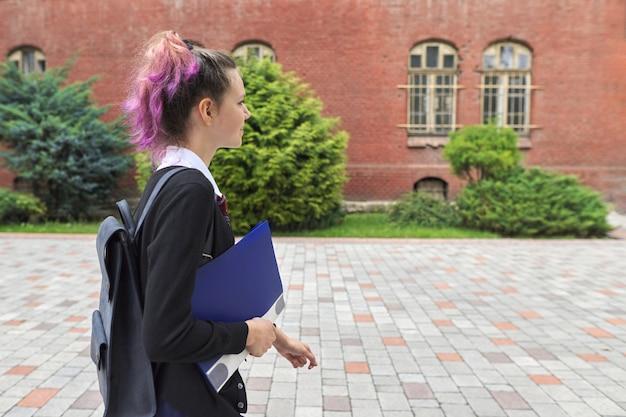Openluchtportret van schoolmeisje dichtbij schoolgebouw Premium Foto