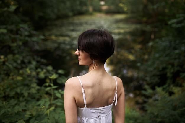 Openluchtportret van tedere kortharige jonge blanke vrouw met bleke huid en slank lichaam ontspannen door vijver in nationaal park Gratis Foto
