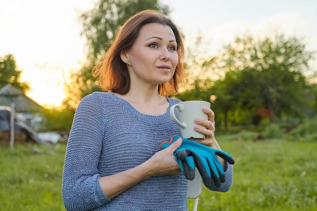 Openluchtportret van vrouw met kop thee, wijfje met handschoenen het rusten Premium Foto