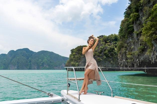 Openluchtschot van aanbiddelijke jonge vrouw in witte beige kleding die zich op rand van jacht bevinden Premium Foto