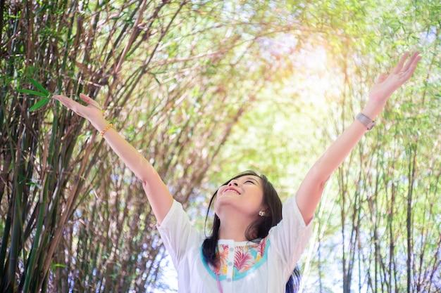 Opgeheven de wapens van de vrijheidsvrouw genietend van de frisse lucht in groene bamboebomen. Premium Foto