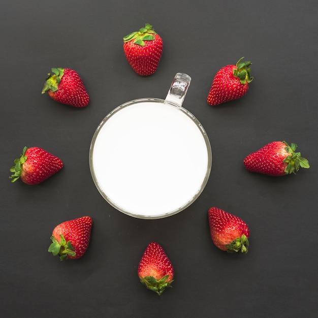Opgeheven mening van aardbeien en melk op zwarte achtergrond Gratis Foto