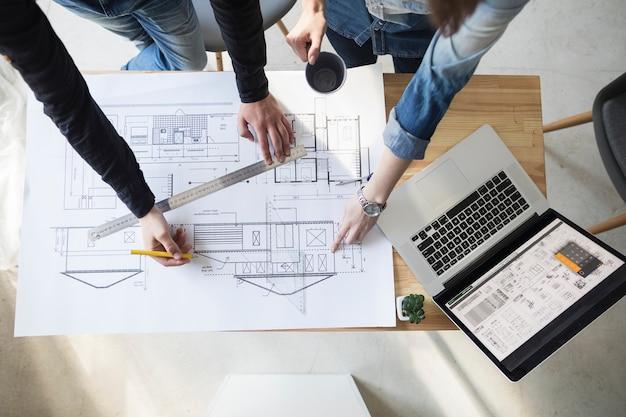 Opgeheven mening van architectenhand die aan blauwdruk over houten bureau op het werk werken Gratis Foto