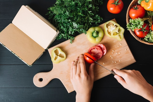 Opgeheven mening van de hand die van een persoon rode tomaat snijdt op hakbord Gratis Foto
