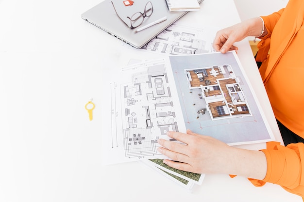 Opgeheven mening van de vrouwelijke blauwdruk van de handholding op wit bureau Gratis Foto
