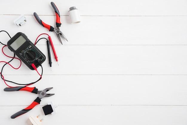 Opgeheven mening van digitale multimeter en elektrisch materiaal op wit houten bureau Gratis Foto