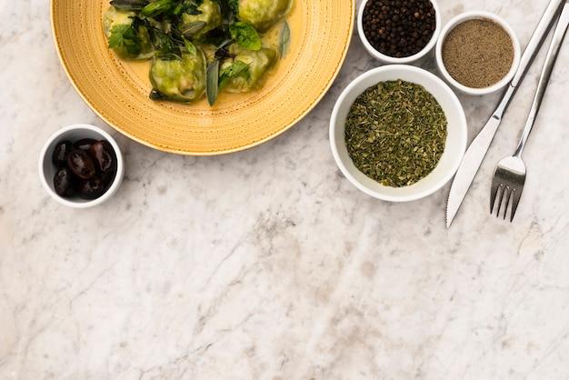 Opgeheven mening van groene raviolideegwaren en ruw ingrediënt op marmeren geweven achtergrond Gratis Foto