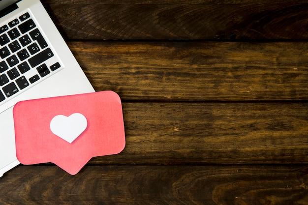 Opgeheven mening van laptop en zoals pictogram op houten lijst Premium Foto