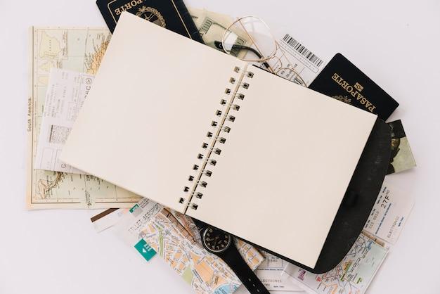 Opgeheven mening van leeg spiraalvormig notitieboekje op paspoorten en kaarten tegen witte achtergrond Gratis Foto
