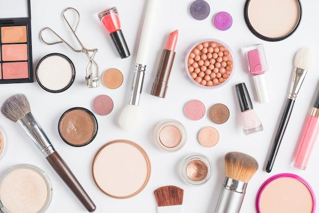Opgeheven mening van make-upuitrustingen op witte achtergrond Gratis Foto