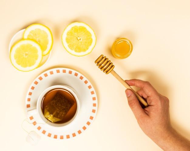 Opgeheven mening van menselijke de honingsdipper van de handholding dichtbij gezonde thee en citroenplak Gratis Foto