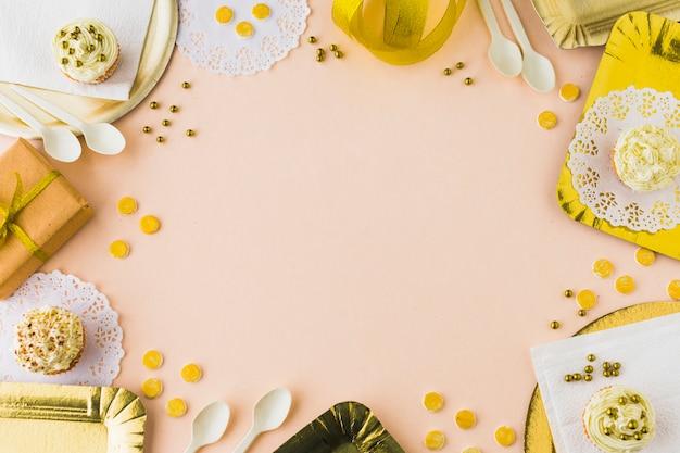 Opgeheven mening van muffins en giften op gekleurde achtergrond Gratis Foto