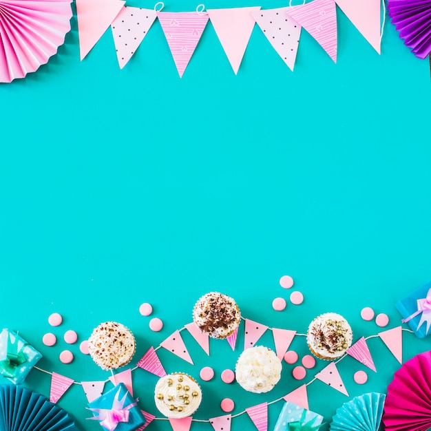 Opgeheven mening van muffins met partijtoebehoren op groene achtergrond Gratis Foto