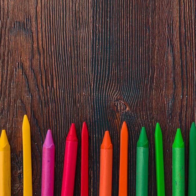 Opgeheven mening van multicolored waskleurpotloden op bruine plank Gratis Foto