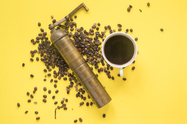 Opgeheven mening van oude koffiemolen en koffiebonen met hete koffie op gekleurde achtergrond Gratis Foto