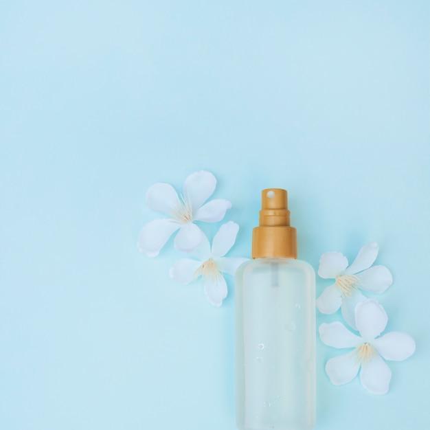 Opgeheven mening van parfumfles en witte bloemen op blauwe oppervlakte Gratis Foto