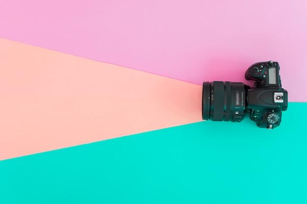 Opgeheven mening van professionele camera op gekleurde achtergrond Gratis Foto