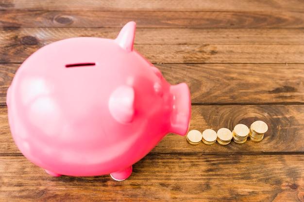 Opgeheven mening van roze piggybank die dichtbij gestapelde muntstukken verhoogt Gratis Foto