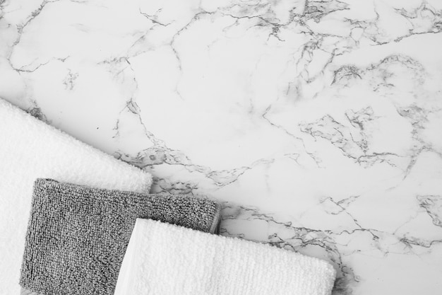 Opgeheven mening van witte en zwarte handdoeken op marmeren achtergrond Gratis Foto