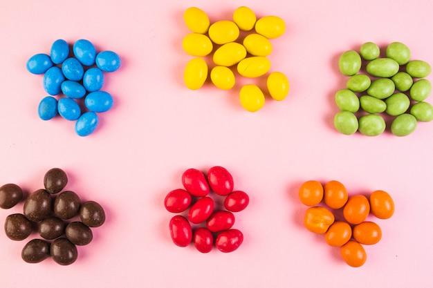 Opgeheven mening van zoet kleurrijk suikergoed op roze achtergrond Gratis Foto