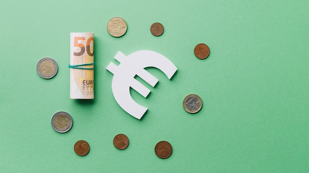 Opgerold bankbiljet met muntstukken en euro teken op groene achtergrond Gratis Foto