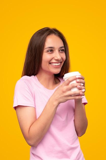 Opgetogen jonge vrouw glimlachte en kijkt weg terwijl ze geniet van verse koffie om 's ochtends tegen een gele achtergrond te gaan Premium Foto