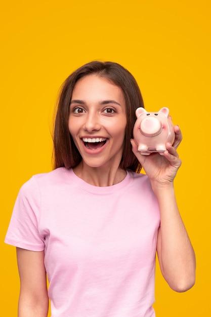 Opgetogen jonge vrouw in roze t-shirt camera kijken met geopende mond en spaarpot tegen gele achtergrond demonstreren Premium Foto