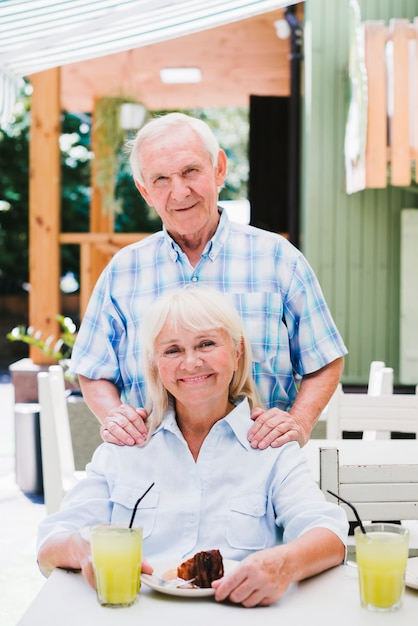 Opgetogen oud paar die in koffie op terras koesteren die van verfrissende drank en cake genieten Gratis Foto
