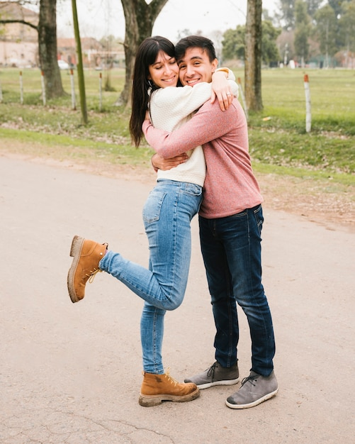 Opgetogen paar dat zich op asfalt en het koesteren bevindt Gratis Foto