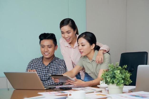 Opgewekte aziatische collega's die laptop het scherm samen in bureau bekijken Gratis Foto