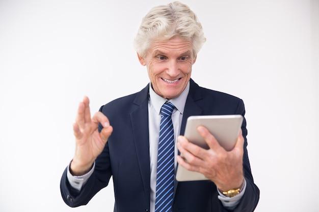 Opgewekte hogere zakenman kijken naar touchpad Gratis Foto